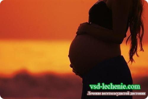 Беременная женщина на закате